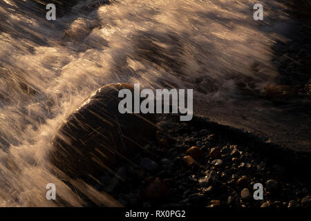 Sintra Cascais Natural Park, Portugal - 07 July 2018: Waves crashing on the rocks at Grota Beach - Stock Photo