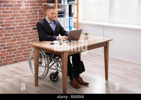 Disabled Businessman Sitting On Wheelchair Using Laptop At Workplace - Stock Photo