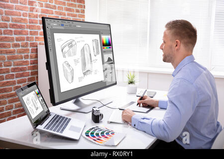 Side View Of Designer Drawing Suitcase On Computer Using Graphic Tablet In Office - Stock Photo