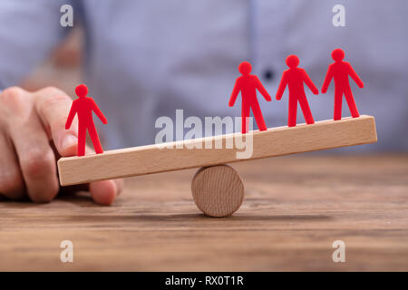 Businessperson's Hand Showing Imbalance Between Red Figures On Seesaw Over Wooden Desk - Stock Photo