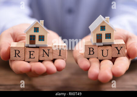 Close-up Of A Businessman's Hand Balancing Rent And Buy Blocks With House Model - Stock Photo