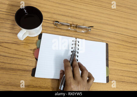 Businessman writing in his diary. Open notebook with blank pages next to cup of coffee and eyeglasses on wooden table. Business still life concept wit - Stock Photo