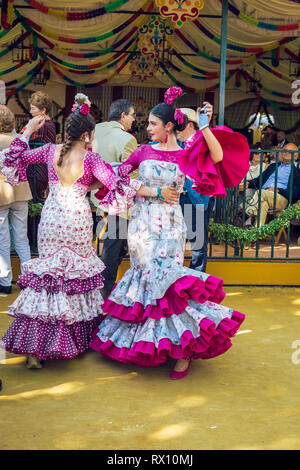 Young women wearing flamenco dresses and dancing 'Sevillanas' at the April Fair, Seville Fair (Feria de Sevilla). - Stock Photo