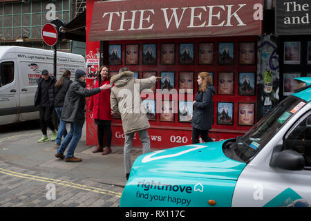 A passer-by offers directions to a couple on the street corner of Berwick and Broadwick Streets on 5th March 2019, in London, England. - Stock Photo