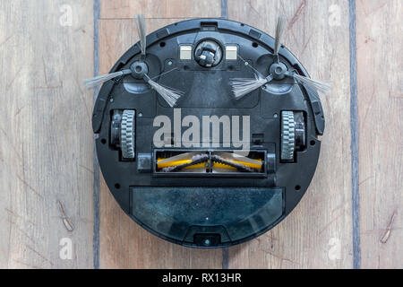Robot vacuum cleaner upside down on the floor. Covered with dust after cleaning. - Stock Photo