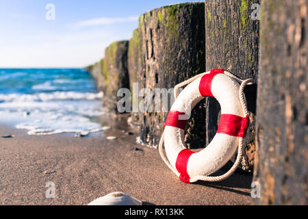 Vintage red and white miniature life buoy at row of groynes on sandy shore of baltic sea (copy space) - Stock Photo