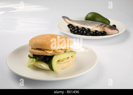 fish burger with avocado and olives, slices of cheese, seasoned with sauce and green salad for a restaurant menu on a white isolated background - Stock Photo