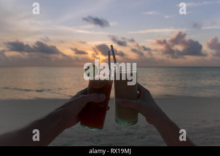 two glasses of cocktail making cheers during sundown - Stock Photo