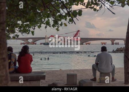 people taking a bath in the sea. Sinamalé Bridge as background - Stock Photo