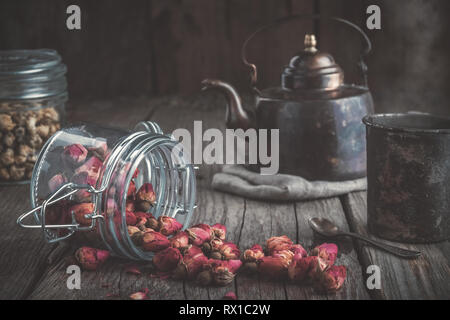 Vintage teapot, cup of healthy herbal tea, glass jars of dry rose buds and daisy medicinal herbs tea. - Stock Photo