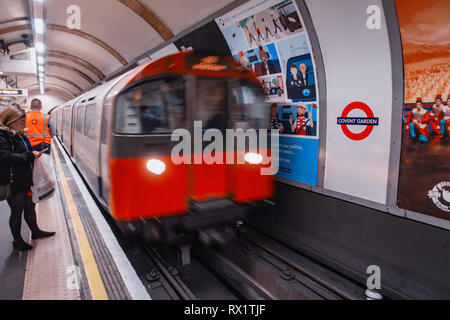 Female Commuter waits for the approaching tube train on london underground track passing ad poster - Stock Photo