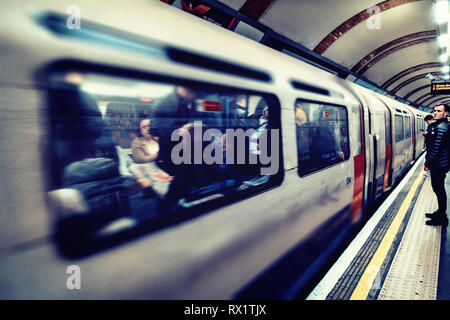 Male Commuter waits for the approaching fast moving tube train - Stock Photo
