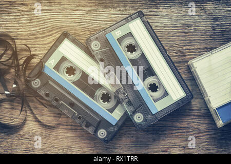 Two vintage audio cassette tapes on wooden background. - Stock Photo