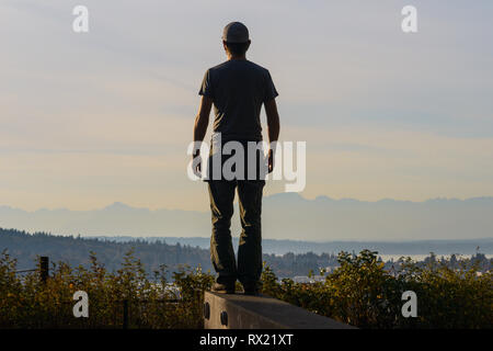 Rear view of man looking at view while standing on retaining wall against cloudy sky during sunset - Stock Photo
