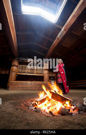 A first nations elder dressed in her traditional regalia stands beside a fire in the bighouse in the village of Oweekeno.  Wuikinuxv, Rivers Inlet, Br - Stock Photo