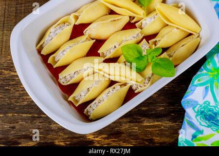 Textured stuffed served in casserole dish full of jumbo shells pasta - Stock Photo