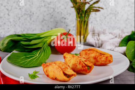 Big pasta shells staffed with cheese and tomato sauce meat - Stock Photo