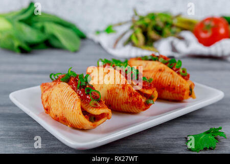 Shells pasta stuffed with minced beef meat with herbs and tomato sauce - Stock Photo