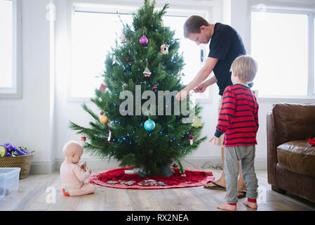 Father decorating Christmas tree while standing with children at home - Stock Photo