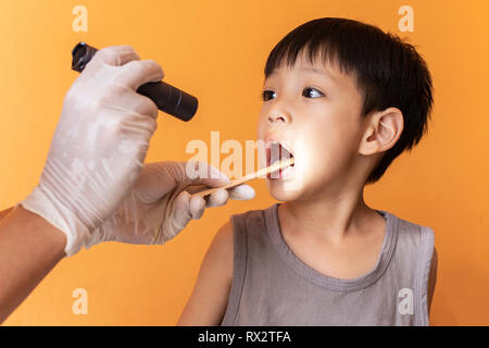 Close up doctor examining throat of patient with tongue depressor. - Stock Photo