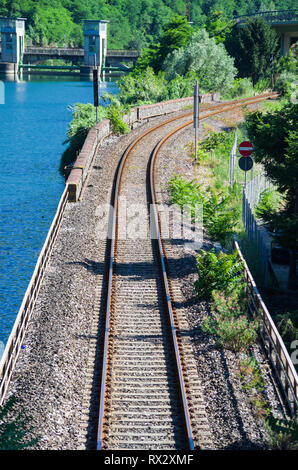 Old railroad tracks run along the blue lake in the green mountains - Stock Photo