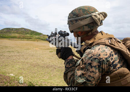 A U.S. Marine with Fox Company, 2nd Battalion, 3rd Marine Regiment, III Marine Expeditionary Force, aims and fires a M203 Grenade Launcher at targets during a squad supported attack at the Kaneohe Bay Range Training Facility, Marine Corps Base Hawaii, Mar. 6, 2019. Fox utilized machine gun suppression and mortar fire on simulated enemy forces, while infantrymen assaulted forward towards them. This combined-forces exercise was the first day of the battalion's training event, Exercise Bougainville I, an annual training exercise that strengthens pre-deployment readiness. (U.S. Marine Corps photo  - Stock Photo
