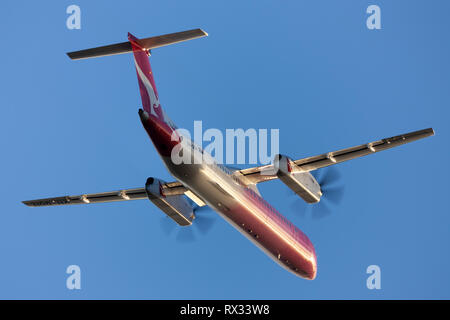 QantasLink Bombardier DHC-8-402 twin engine turboprop regional airliner taking off from Adelaide Airport. - Stock Photo