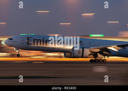 Emirates Airlines Boeing 777-300ER aircraft landing at Adelaide Airport at night. - Stock Photo