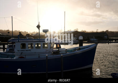 A passenger pleasure boat moored in Yarmouth marina Isle of Wight with the setting sun glowing orange in the west background. - Stock Photo
