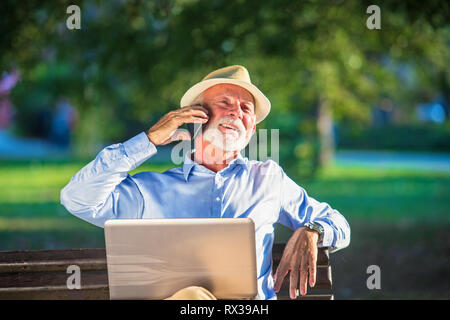 Business correspondence. Focused mature businessman using laptop while sitting in park - Stock Photo