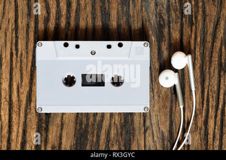 Overhead shot of retro old audio cassette tape with earphone on grunge vintage wood background, top view - Stock Photo