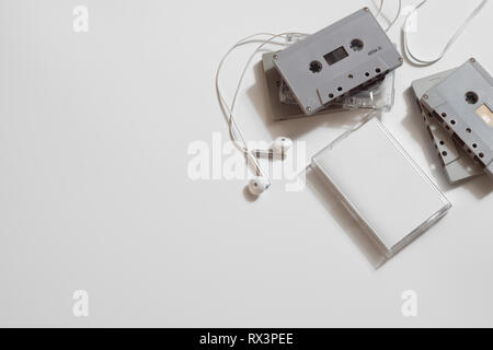 Overhead shot of retro old audio cassette tape with earphone on white background, flat lay top view with copy space. - Stock Photo