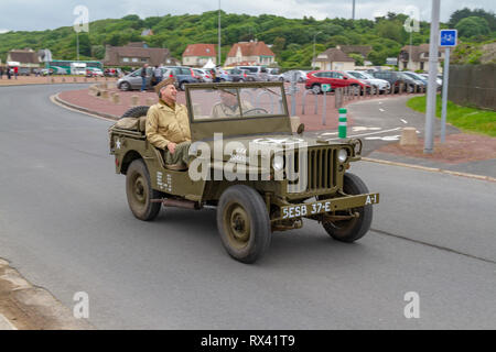Re-enactors in a World War II American jeep on the seafront of Omaha Beach close to Vierville Sur Mer, Normandy, France. - Stock Photo