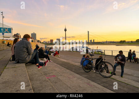 DUSSELDORF, GERMANY - CIRCA SEPTEMBER, 2018: people sitting on the steps down to the promenade by the Rhine River in Duesseldorf - Stock Photo