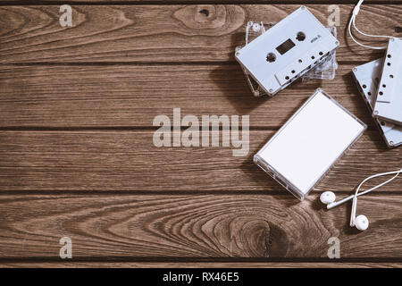Overhead shot of retro old audio cassette tape with earphone on vintage retro wooden background, flat lay top view with copy space. - Stock Photo