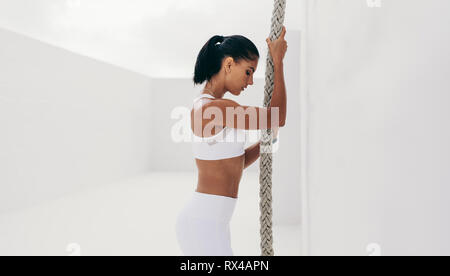 Side view of a woman in fitness wear standing holding a rope. Athletic woman getting ready to climb a hanging rope. - Stock Photo