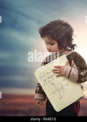 Portrait of Sad little toddler girl holding blank book standing in sunset light - Stock Photo