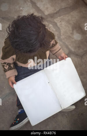 High angle view of Cute 2 year little Indian Asian baby girl kid with blank book while sitting on the floor. - Stock Photo