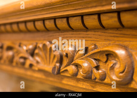 Close-up detail of carved wooden decorative piece of furniture with floral ornament made of natural hardwood. Art craft and design concept. - Stock Photo