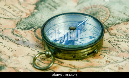 A round compass with its pointer moving pointing to some directions. - Stock Photo