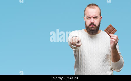 Young hipster man eating chocolate bar over isolated background pointing with finger to the camera and to you, hand sign, positive and confident gestu - Stock Photo