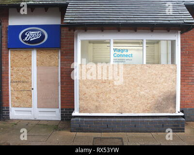 Ashbourne Shrovetide Football 2019. Shops boarded up prior to Ash Wednesday match including branch of Boots chemist advertising Viagra. - Stock Photo