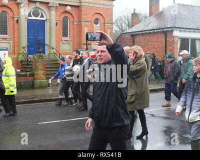 Ashbourne Shrovetide Football 2019. Local firefighter Paul Holmes is escorted through the town to turn up the ball for the Ash Wednesday Game. - Stock Photo