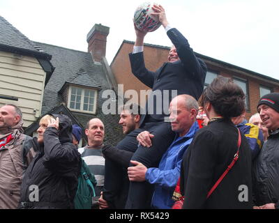 Ashbourne Shrovetide Football 2019. Local firefighter Paul Holmes is paraded with the ball he will turn up to begin the Ash Wednesday Game. - Stock Photo