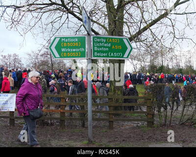 Ashbourne Shrovetide Football 2019. A spectator picks her way through the crowds and mud past a signpost to other local towns on Ash Wednesday - Stock Photo