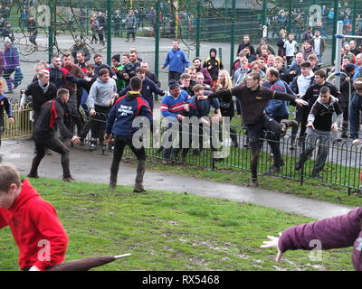 Ashbourne Shrovetide Football 2019. Players scramble to follow the ball as play enters a children's playground during the Ash Wednesday game. - Stock Photo