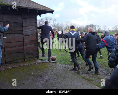 Ashbourne Shrovetide Football 2019. A sight of the ball as play enters the town playing fields during the Ash Wednesday match. - Stock Photo