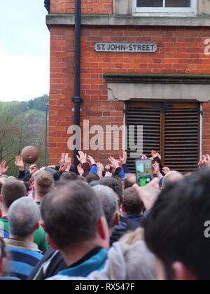 Ashbourne Shrovetide Football 2019. Hands in a sea of players grasp for the ball on St John Street as play enters town during the Ash Wednesday game. - Stock Photo