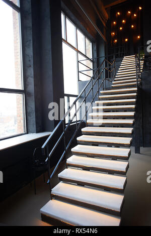 High black metal staircase with wooden steps in loft style room - Stock Photo