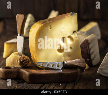 Piece of cow's milk Maasdam cheese on wooden board. Range of cheeses at the background. - Stock Photo